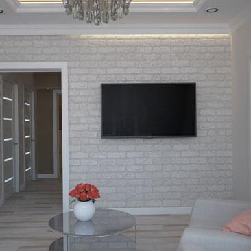 Гостиная со светлой кирпичной стеной.