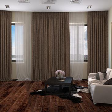 Гостиная с двумя окнами и коричневыми шторами.